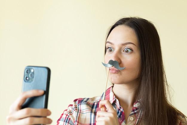 Fille s'amuser et prendre selfie, fille avec une drôle de moustache noire, concept de vacances de jour d'imbéciles