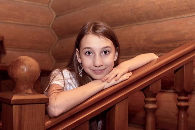 La fille s'appuie sur une échelle en bois dans une maison en rondins.