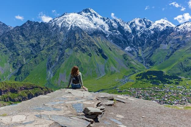 La fille s'assied sur le bord des falaises et regarde les sommets des montagnes près du village de gergeti en géorgie