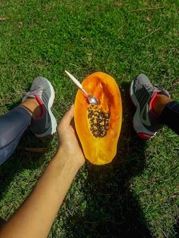 La fille s'assied sur une pelouse et tient une moitié de papaye délicieuse avec une cuillère