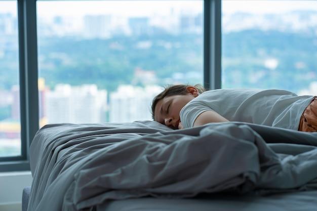La fille s'est accidentellement endormie dans son lit à midi. la fille dort l'après-midi dans des vêtements. sommeil de jour réparateur court.
