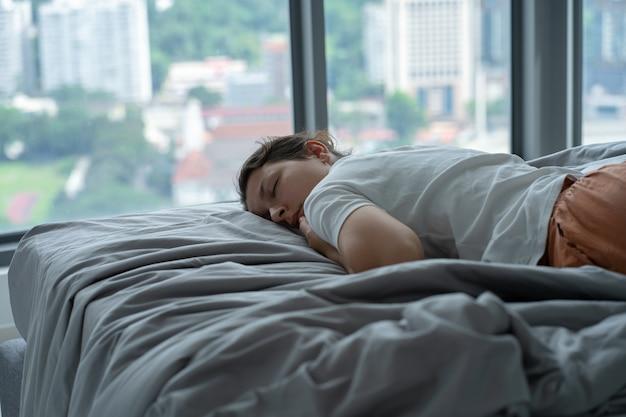 La fille s'est accidentellement endormie dans son lit à midi. la fille dort l'après-midi dans des vêtements