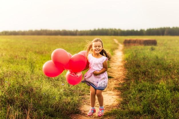 Fille s'exécute avec des ballons rouges en été dans la nature