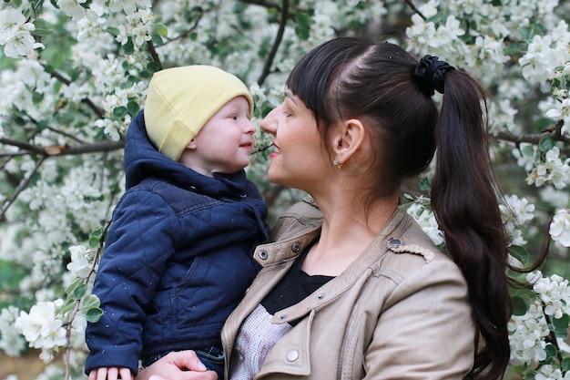 Fille avec sa fille dans un jardin de fleurs de pommiers au printemps