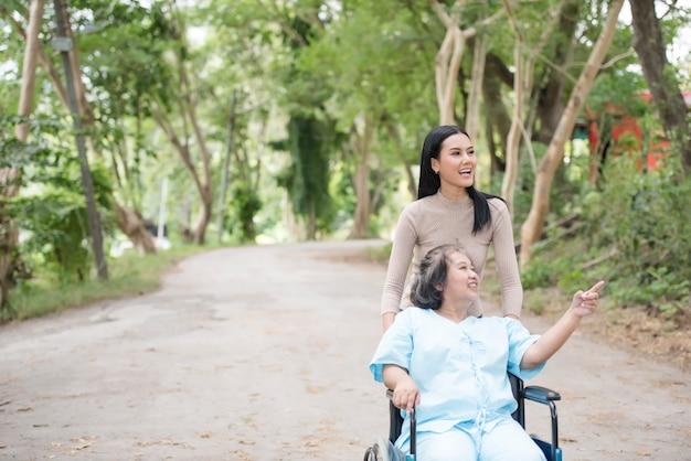 Fille avec sa mère assise dans un fauteuil roulant