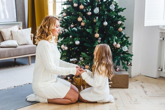 Une fille avec sa mère près de l'arbre de noël, intérieur décoré pour noël