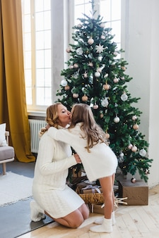 La fille et sa mère se regardent, communiquent et la fille joue avec les cheveux de sa mère, la mère et la fille habillent le sapin de noël