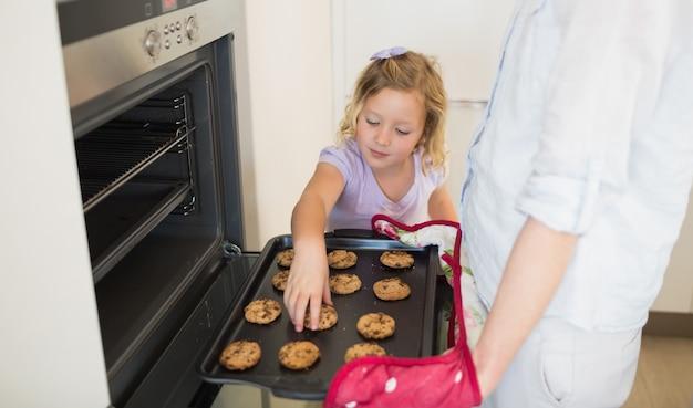 Fille avec sa mère en train de préparer des biscuits