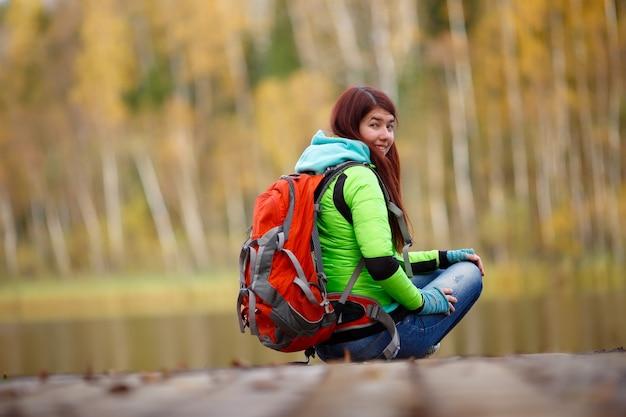 Fille avec sac à dos assis sur le pont au bord du lac