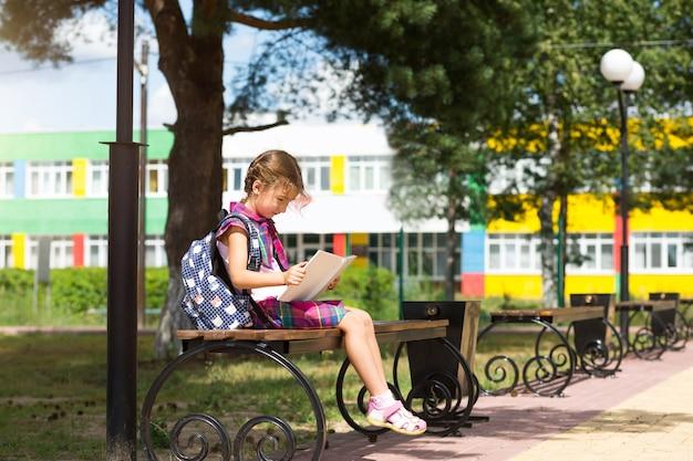Fille avec un sac à dos assise sur un banc et lisant un livre près de l'école. retour à l'école, horaire des cours, un journal avec les notes. éducation, classes de primaire, 1er septembre