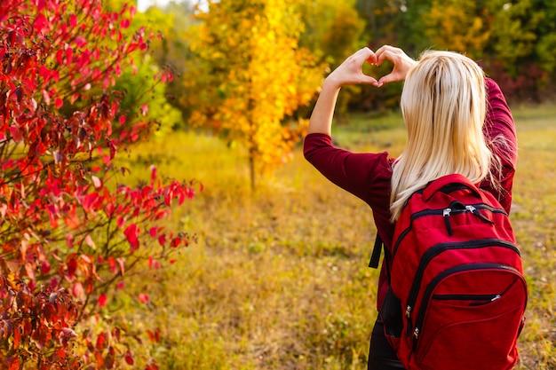 Fille avec un sac à dos montre un coeur dans le parc en automne