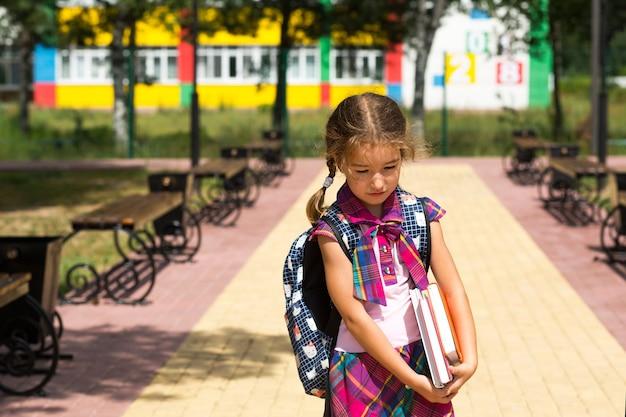 Fille avec un sac à dos et une pile de livres près de l'école. de retour à l'école, l'enfant est fatigué, les manuels lourds. scolarité, classes de primaire, rentrée scolaire, 1er septembre