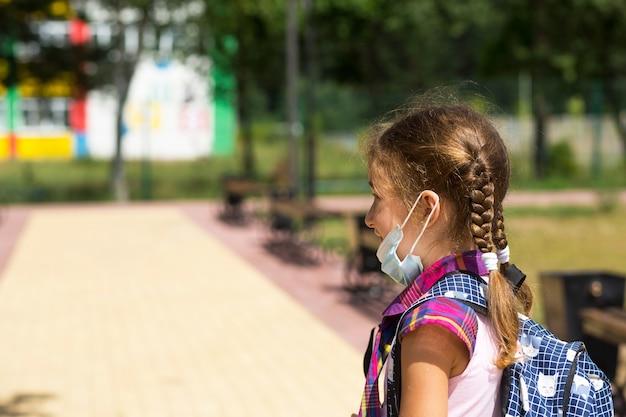 Fille avec un sac à dos près de l'école après les cours avec le masque médical retiré