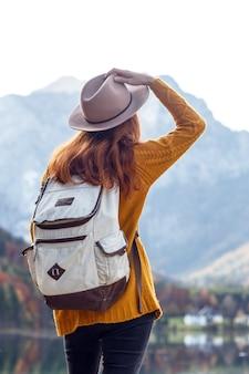 Fille avec un sac à dos se dresse sur la rive d'un lac de montagne