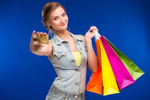 Fille avec des sacs et une carte de crédit dans les mains