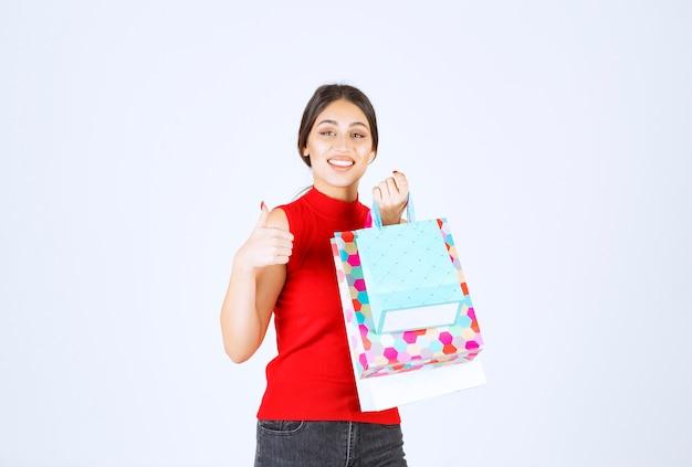 Fille avec des sacs colorés se sentant positive.