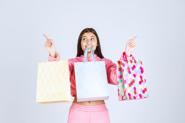 Fille avec des sacs colorés les tenant dans les mains et la bouche.