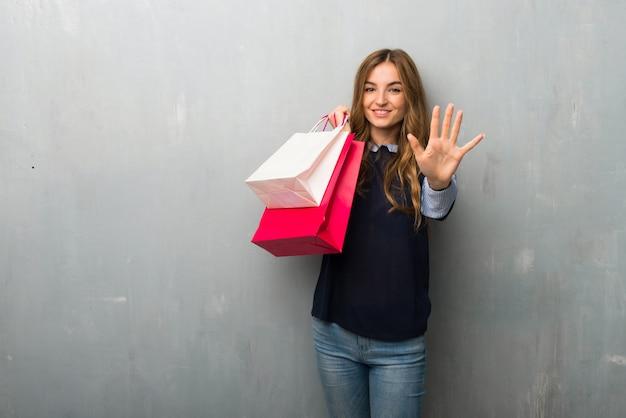 Fille avec des sacs à provisions comptant cinq avec les doigts
