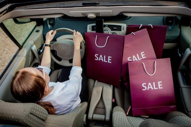 Une fille avec des sacs à provisions conduit une voiture, concept de rabais et de shopping, vue de dessus