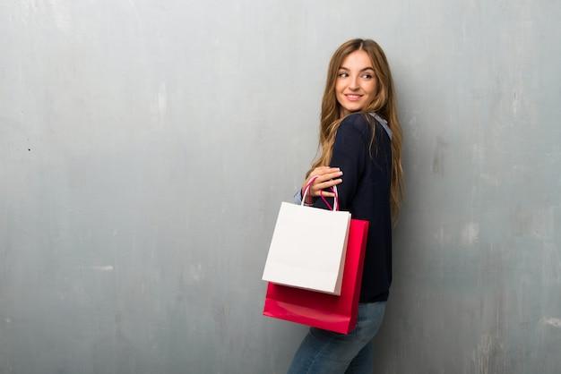 Fille avec des sacs à provisions regardant par-dessus l'épaule avec un sourire