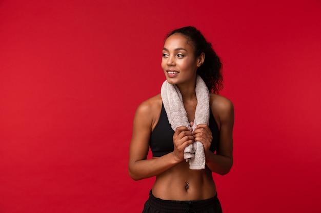 Fille saine afro-américaine des années 20 en sportswear noir avec une serviette sur son cou debout, isolé sur mur rouge