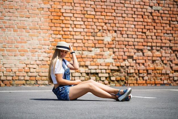Fille en salopette en jean, un t-shirt blanc et un chapeau léger sur fond d'un bâtiment en brique sous le soleil éclatant