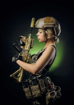 Fille en salopette militaire airsoft posant avec une arme à feu dans ses mains