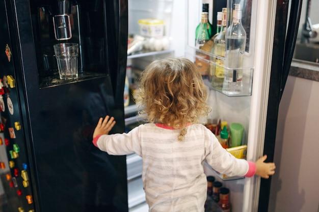 Fille sans visage regardant à l'intérieur du réfrigérateur