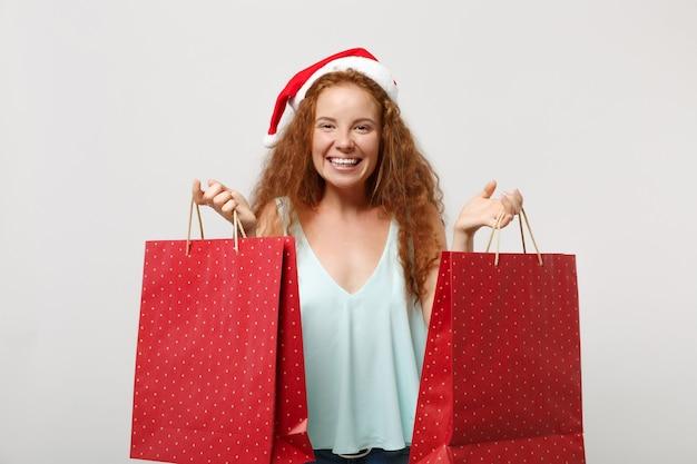 Fille de santa rousse souriante au chapeau de noël isolé sur fond blanc. concept de vacances de célébration de bonne année 2020. maquette de l'espace de copie. tenez les sacs d'emballage avec des cadeaux ou des achats après le shopping.