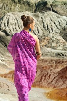 Une fille en sari rose se tient à l'extérieur sur fond de paysage désertique