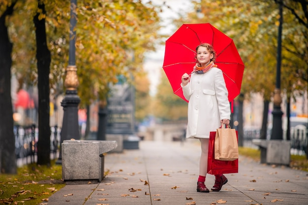 Fille satisfaite avec un parapluie rouge et des paquets de shopping va sur la rue de la ville d'automne