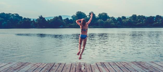 Fille sautant dans l'eau