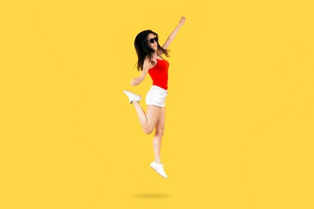 Fille sautant dans des lunettes de soleil et une chemise rouge sur un mur jaune, ambiance d'été concept