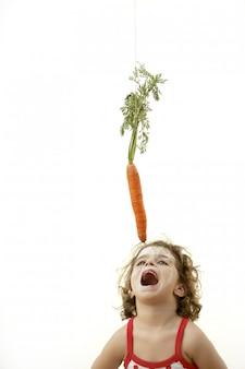 Fille sautant pour manger le piège à carottes de lapin