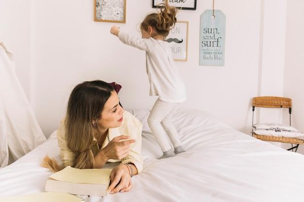Fille sautant près de lire mère