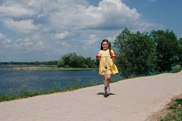 Une fille sur un scooter un week-end en famille dans un mini voyage local un scooter pour enfants comme symbole de famille ...