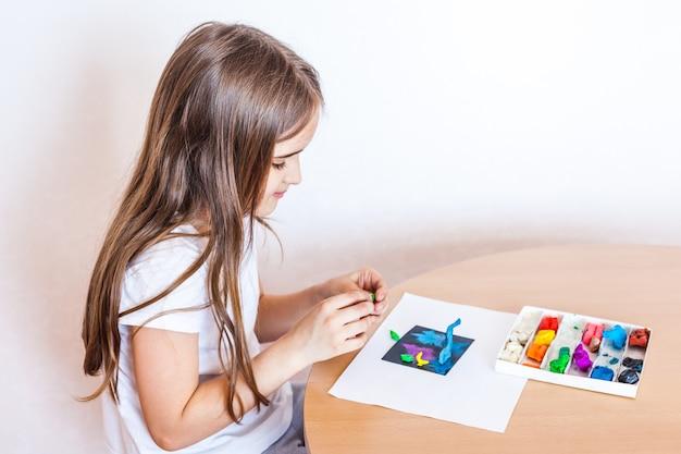Fille sculpte de pâte à modeler, d'argile, de pâte, de bricolage à la maison, de créativité pendant les vacances