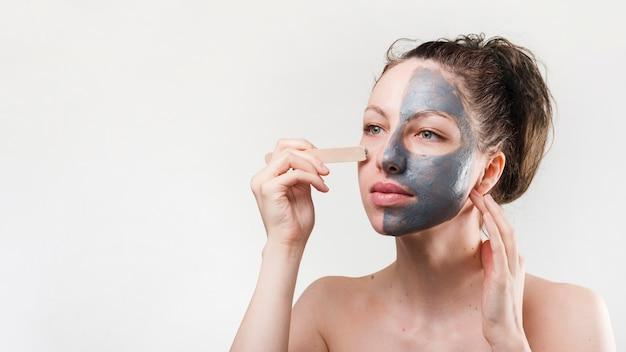 Fille se appliquant un produit cosmétique