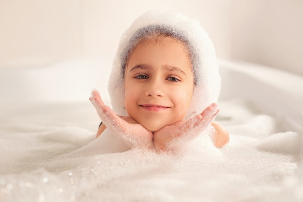 Fille se baignant et jouant avec de la mousse dans la salle de bain