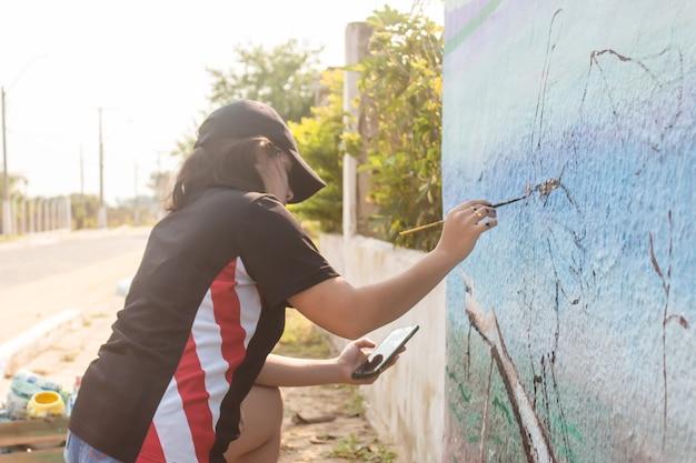 Fille se concentrant sur la peinture d'un mur de rue avec son téléphone portable comme référence.