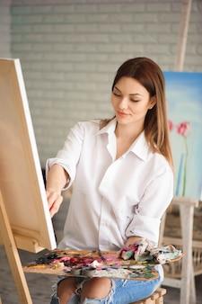 Fille se concentrant sur la toile d'art tout en peignant