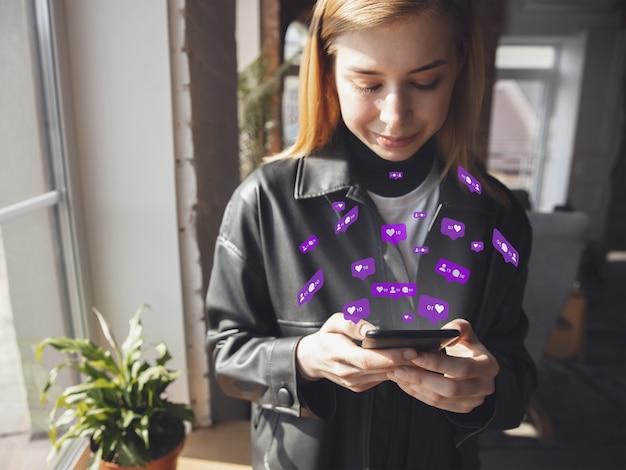 Fille se connectant et partageant avec les médias sociaux, faisant défiler le smartphone. obtient des commentaires, aime. icônes d'interface utilisateur modernes, communication, appareils. concept de technologies modernes, de mise en réseau, de gadgets. concevoir.