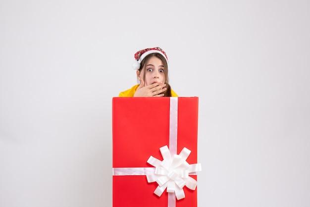 Fille se demande avec bonnet de noel debout derrière un grand cadeau de noël sur blanc