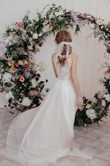 La fille se déplace magnifiquement dans une longue robe élégante blanche