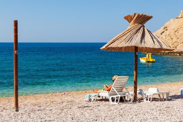 Fille se détendre sur la chaise longue en lisant un livre sous un parapluie de paille sur la plage d'oprna