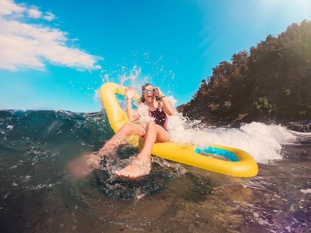 Fille se faire éclabousser par les grosses vagues
