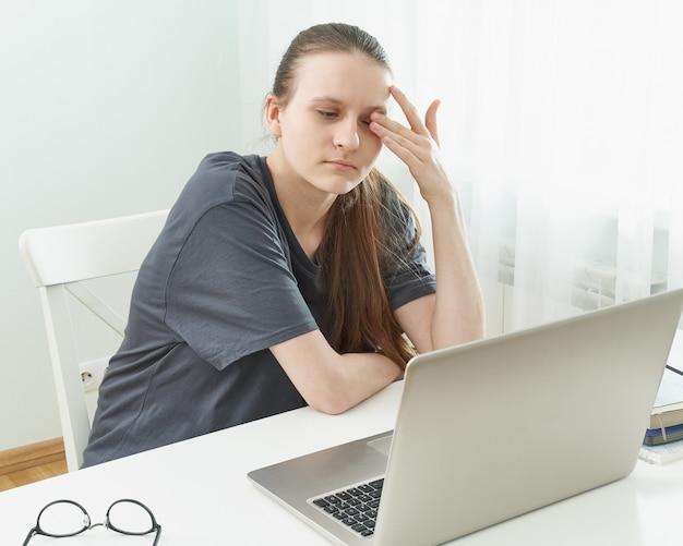 La fille se frotte les yeux, ses yeux sont fatigués de la tension et de la douleur.