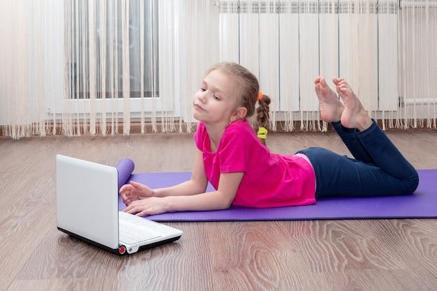 Fille se penche sur une leçon en ligne pour ordinateur portable et fait des exercices de remise en forme
