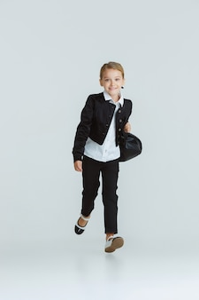 Fille se préparant à l'école après une longue pause estivale. retour à l'école. petit modèle caucasien féminin posant en uniforme scolaire sur un mur blanc. enfance, éducation, concept de vacances.