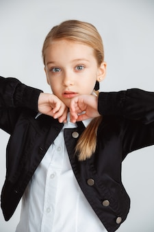 Fille se préparant à l'école après une longue pause estivale. retour à l'école. petit modèle féminin caucasien posant en uniforme scolaire sur fond de studio blanc. enfance, éducation, concept de vacances.